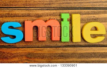 Colorful letters Smile word on wooden table