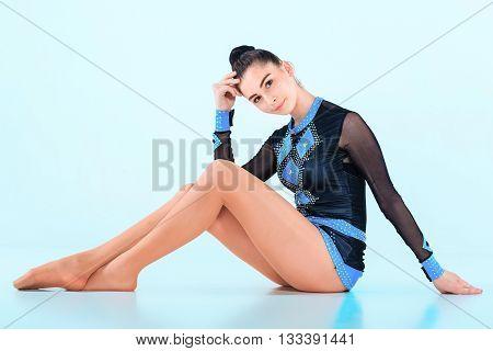 The girl sitting after gymnastics dance on blue background