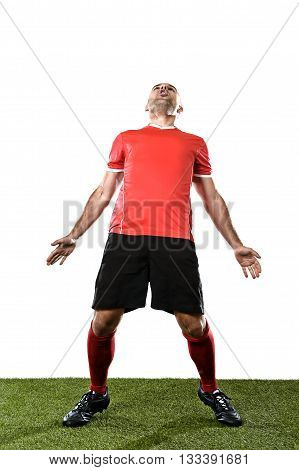 young happy football player in red jersey screaming excited on grass pitch celebrating scoring goal opening his arms isolated on white background