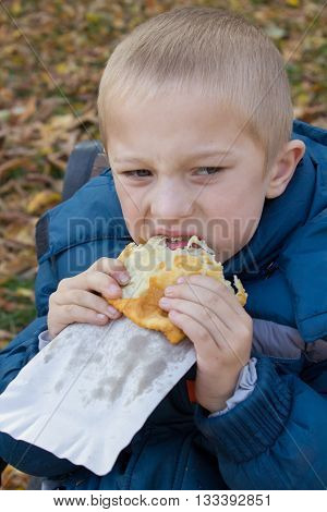 close-up of a boy biting big delicious pasties