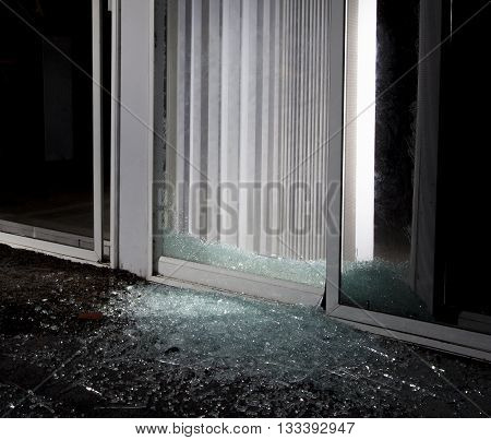 Shattered sliding glass door at night after a break in