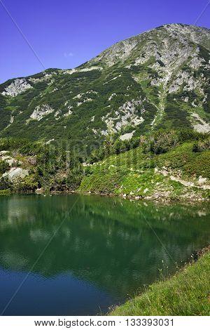 Reflection of Hvoynati peak in Okoto lake, Pirin Mountain, Bulgaria
