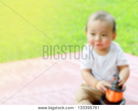 blurred portrait Asian boy hold pumpkin doll in hand with grasses background soft focus sleepy emotion