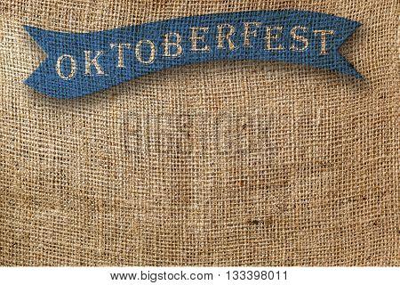oktoberfest written blue ribbon on jute background