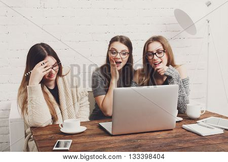 Three girls have coffee with laptop. Young girls friends watch something in internet. Shocking news. Girls are amused, laughing, ashamed, surprised. Women and computer, internet news, gossip concept.