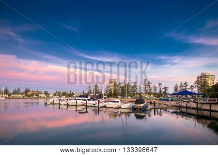 Adelaide Australia - November 8 2014: Boats parked in the docks of Patawalonga lake at Glenelg on a beautiful evenning with sunset sky in the background.