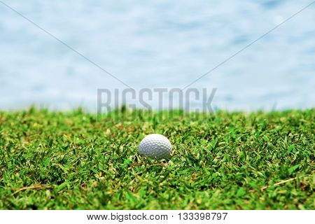 Golf ball on fresh green grass near water bunker in golf course.