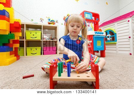 Fascinated Child Playing With Wooden Sticks In Kindergarten