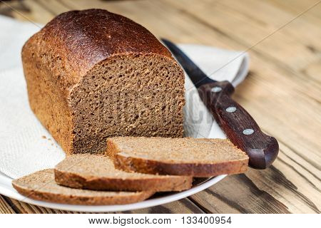 Loaf Of Sliced ​​brown Bread In Bowl On Wooden Table