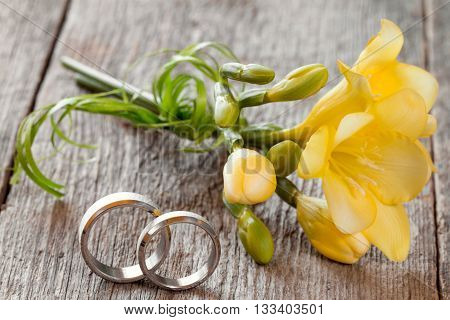 Wedding rings with freesia flower on wooden background
