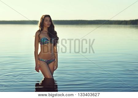 Stunning beautiful girl posing in blue bikini in the lake. Young sexy woman. Full length portrait at sunset with soft lightning