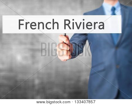 French Riviera - Businessman Hand Holding Sign