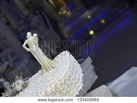 icture of a White Wedding cake with figurine of bride and groom kissing