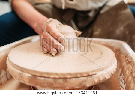 Spinning potters wheel with clay and hand. Close-up of craftsman hand on clay, shaping it into pottery. Dirty potters hand on loam of clay