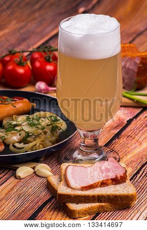 Tall elegant glass with unfiltered white beer with fried sausages tomatoes chery bread garlic and pork meat on the old wooden table - close up portrait photo