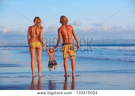 Happy family - father mother baby son hold hands swim with fun walk along sunset sea surf on black sand beach. Travel active parents lifestyle people activity on summer vacations with children.