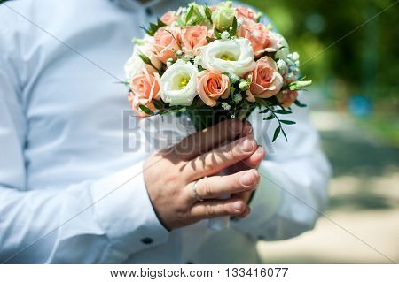 Hand of the groom holding the bride's bouquet