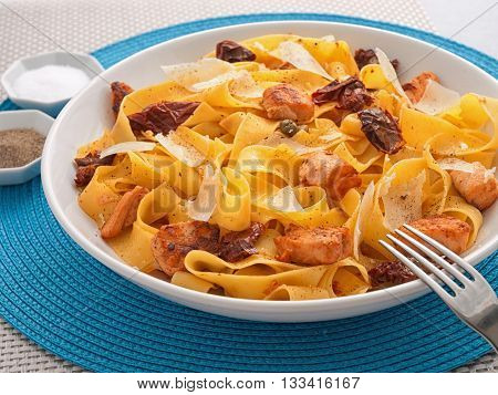 Italian Pasta - fettuccine with dried tomatoes baked salmon and parmesan cheese.