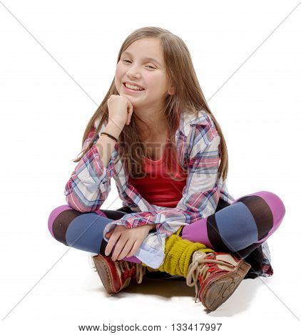 preteen girl in hipster style sitting cross-legged on the floor