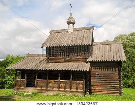 Old Russian wooden log tower with cupolas and crosses among green grass in the summer.