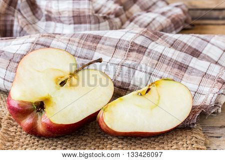 Close up of a sliced red apple on a wooden table. Fresh red apple on old wooden table background. red and green apple on wood table