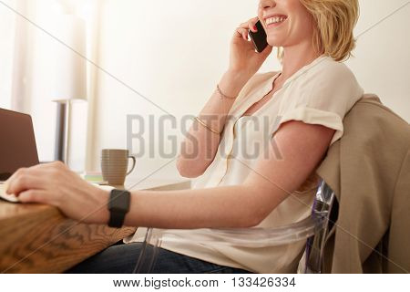 Woman Sitting At A Table And Talking On Mobile Phone