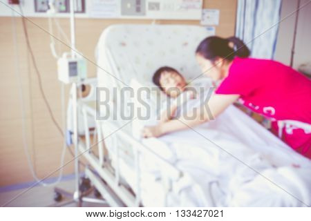 Blurred background of illness asian child admitted at modern and comfortable equipped hospital room. Mother take care her son. Health care and people concept. Vintage style.