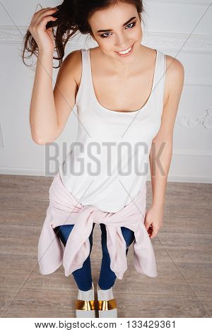 Beautiful happy girl in white T shirt and jeans smiling at the camera in white studio