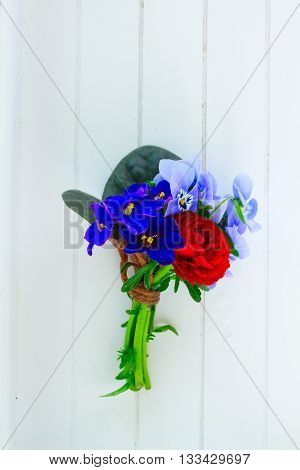 Posy of violets, pansies and ranunculus on white wooden planks background