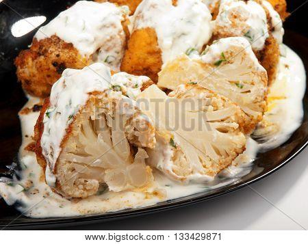 Fried Cauliflower with yogurt garlic sauce. Close up tilted view