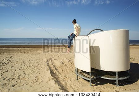 Teenager one on the seashore. Loneliness concept