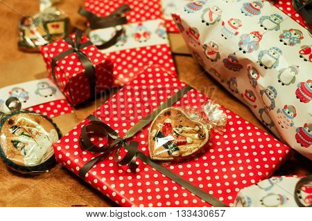Lots of of Christmas gifts in a variety of packaging. White with penguins and red with white polka dots wrapping paper as well as cakes in transparent cellophane.