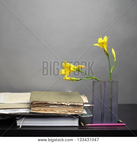 Old books stack next to the vase with yellow flowers front interior shot