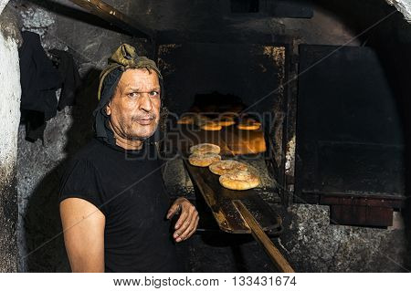 Fez Morocco - April 11 2016: Portrait of a baker standing in front of a traditional oven baking bread in Fez Morocco.