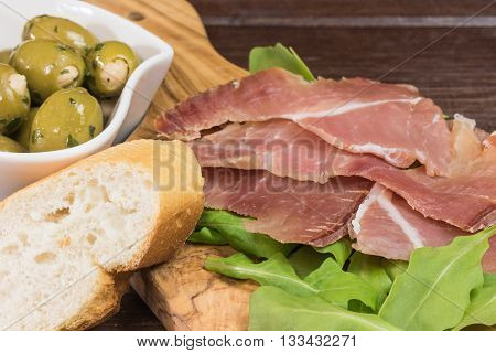 Refreshments of sliced Spanish ham green olives bread and arugula. Everything is lying on a wooden table and in a white bowl.