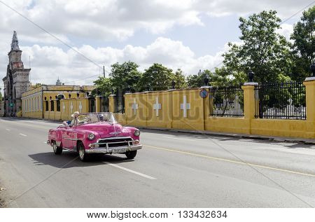 HAVANA - NOVEMBER 29: Pink american classic cabriolet car goes down the street on 29 November 2015 in Havana, Cuba. Brightly colored vintage American cars are very popular in Havana.