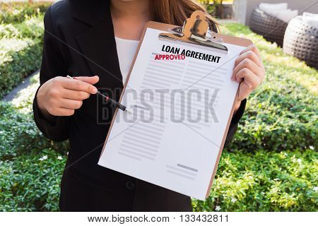Women in suit showing approved loan agreement and pointing with a pencil.