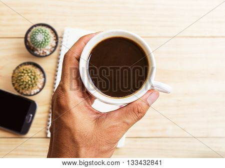 Hand reaching for coffee mug and blurred smart phonenote book on wooden table background. Top view.