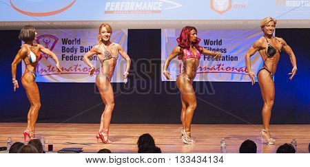 MAASTRICHT THE NETHERLANDS - OCTOBER 25 2015: Female fitness models Gerbel Mikk Sonja den Breems-Tanamal and two other competitors flex their muscles and show their best physique in a side pose on stage at the World Grandprix Bodybuilding and Fitness