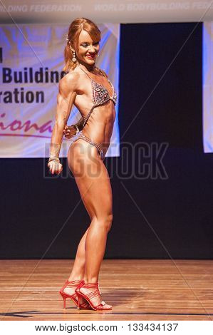 MAASTRICHT THE NETHERLANDS - OCTOBER 25 2015: Female fitness model flexes her muscles and shows her best physique in a triceps pose on stage at the World Grandprix Bodybuilding and Fitness of the WBBF-WFF