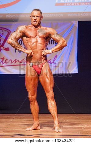 MAASTRICHT THE NETHERLANDS - OCTOBER 25 2015: Male bodybuilder flexes his muscles and shows his best physique in a lats spread pose on stage at the World Grandprix Bodybuilding and Fitness of the WBBF-WFF