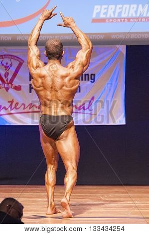 MAASTRICHT THE NETHERLANDS - OCTOBER 25 2015: Male bodybuilder flexes his muscles and shows his best physique in a back pose on stage at the World Grandprix Bodybuilding and Fitness of the WBBF-WFF