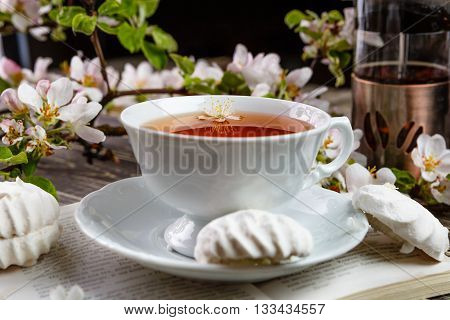 Cup of tea with vanilla zephyr and a book on the old wooden table. Petals and flowers of cherry and apple trees in the spring garden. Rest and relaxation