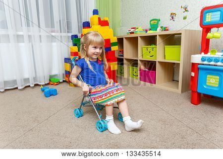 Smiling Little Girl Sitting In Toy Stroller At Home