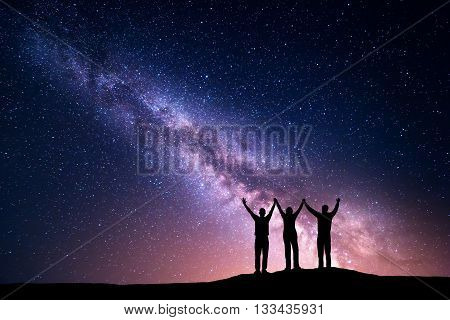 Landscape with colorful Milky Way. Night starry sky with silhouette of a happy family with raised-up arms on the hill. Beautiful Universe. Space background