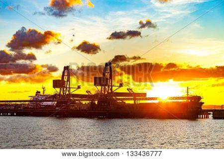 Sea port cranes at sunset in Port of Gdansk Poland.