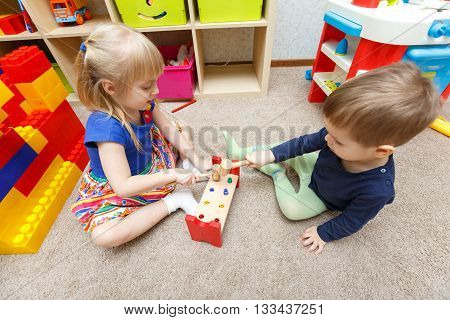 Two Kids Play With Toy Hammers And Sticks In Kindergarten Together