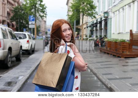 happy teenage girl made a purchase and go through the city streets with packages. The girl has red hair and freckles.