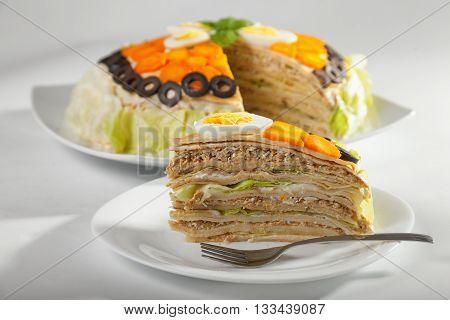 Salty cake made from pancakes tuna fish eggs carrots olives and iceberg salad. Horizontal shot