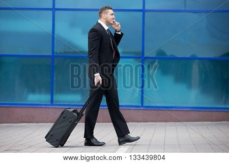 Portrait Of Happy Business Man Walking With Suitcase In A Trip. Copy Space